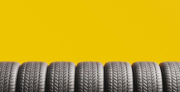 黄色の背景にタイヤが下から覗いていて、テキスト用のスペースがあります。 3dレンダリング