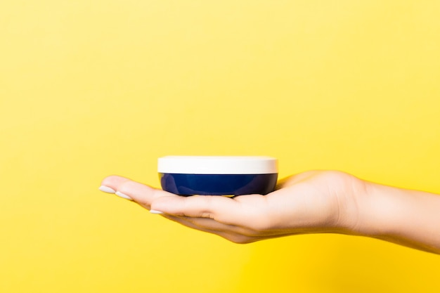 Yellow background with woman's hand holding a cosmetics jar with copy space.