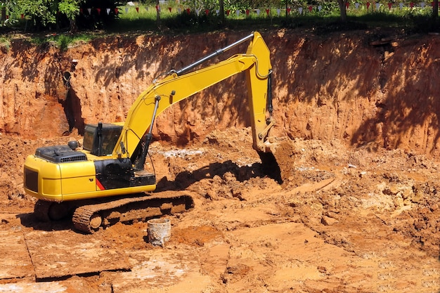 A yellow backhoe is parking in construction site