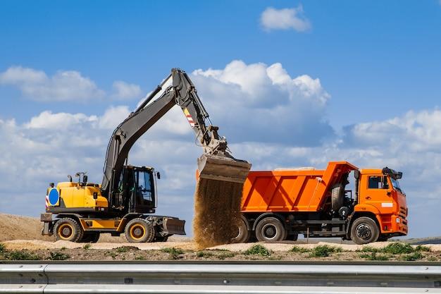Желтый экскаватор-погрузчик загружает землю в грузовик на фоне неба