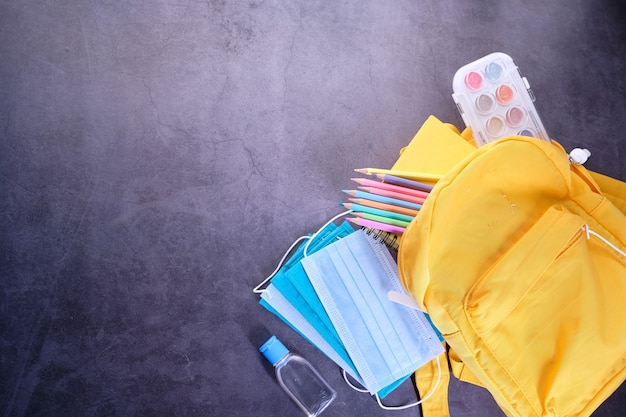 Yellow backpack, stationery, mask and sanitizer on black space .
