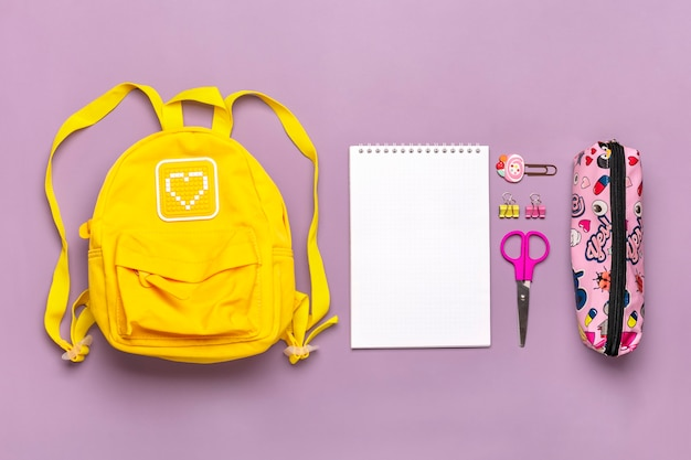 Yellow backpack with school supplies isolated on purple background t