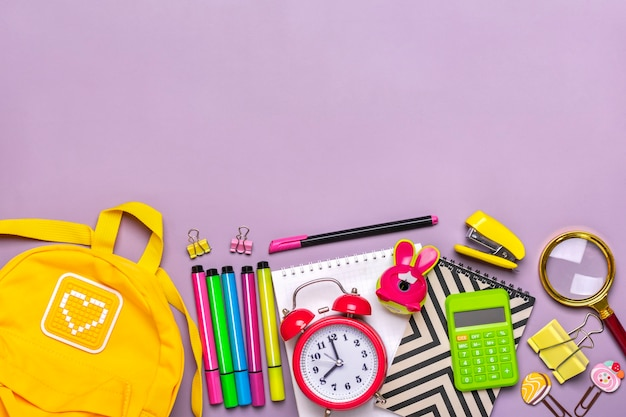 Yellow backpack with school supplies isolated on purple background top view
