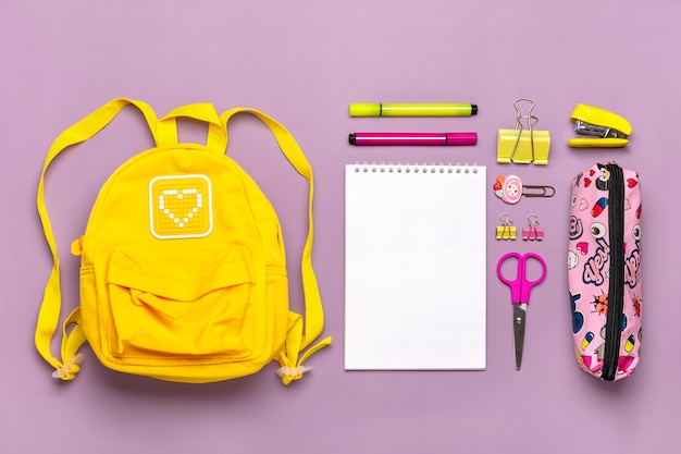 Yellow backpack with school supplies isolated on purple background