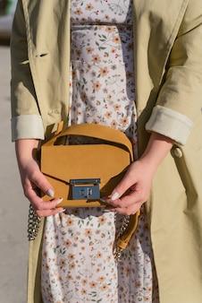 太陽の下で女の子の手に黄色の袋