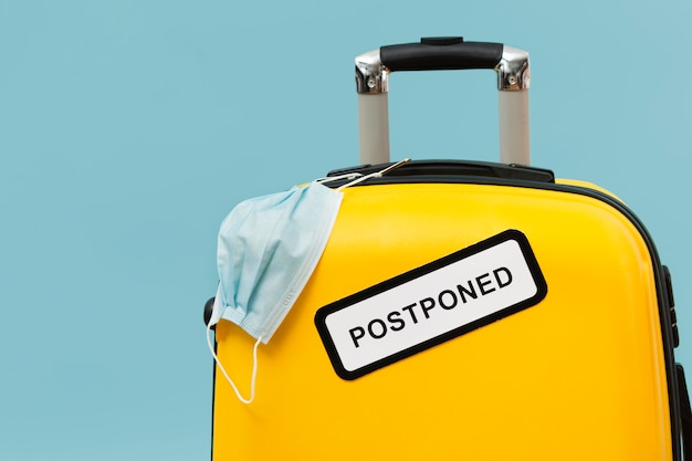 Yellow baggage with postponed sign and medical mask