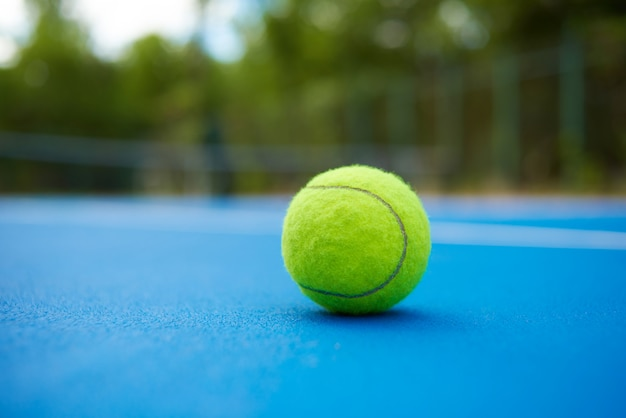 Yellow ball is laying on blue tennis court carpet. blurred green plantings and trees behind.