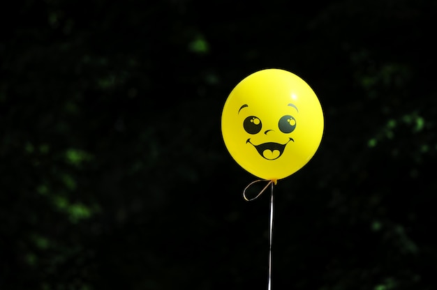 Yellow balloon on a string with a painted face