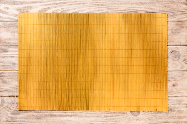 Yellow bamboo mat on wooden background