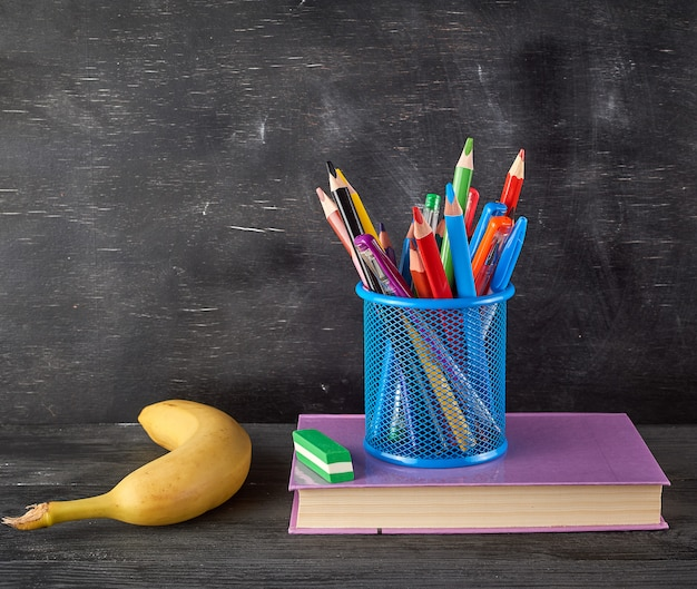 Yellow banana, blue stationery glass with multi colored wooden pencils