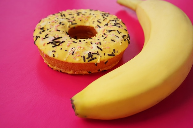 Yellow banana and donut on bright pink background. above view