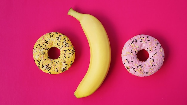 Yellow banana and donuts on bright pink background. above view