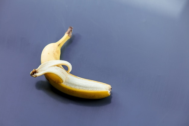 Yellow banana on grey metal background. above view
