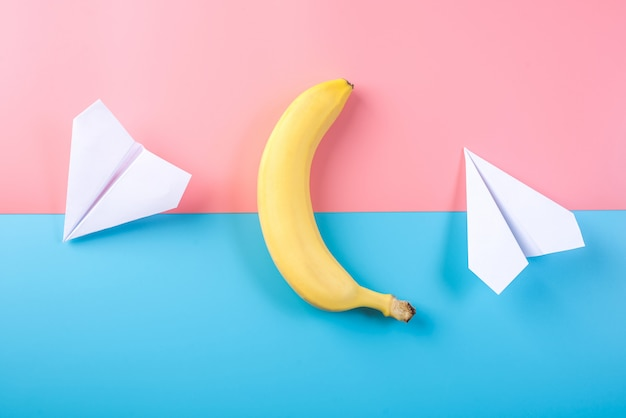 Yellow banana and paper plane on pastel background, top view.