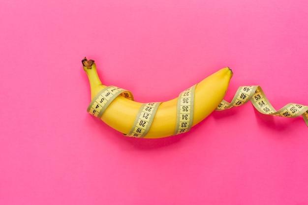 분홍색 배경에 측정 테이프가 있는 노란색 바나나. 남성 페니스 크기 개념입니다. 평평한 평지, 평면도, 복사 공간.
