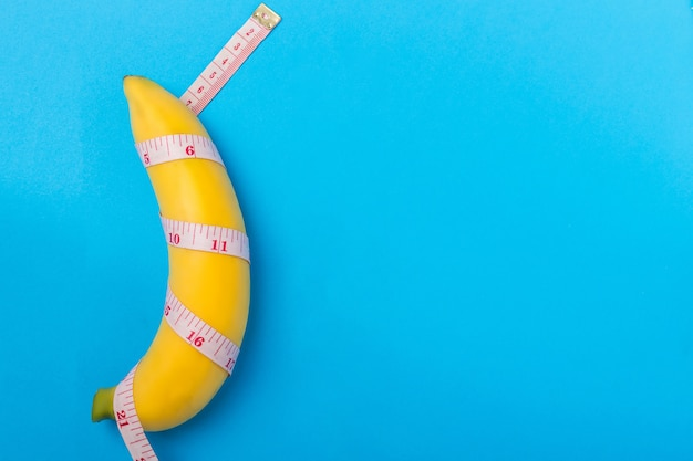 Yellow banana with measurement tape