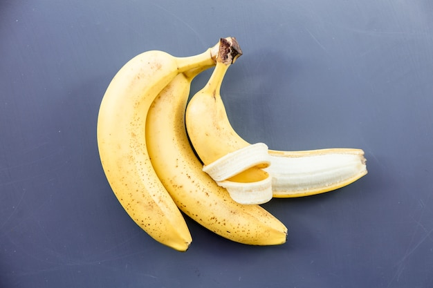 Yellow bananas on grey metal background. above view