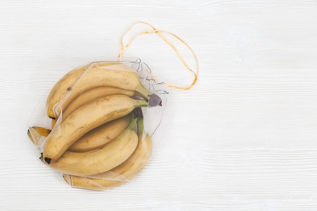 Желтые бананы в многоразовых эко сумках. свежие фрукты в пакетиках из прозрачного текстиля для хранения продуктов. пластиковая бесплатная концепция.