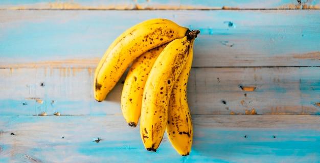 青い木製のテーブルの背景に黄色のバナナ