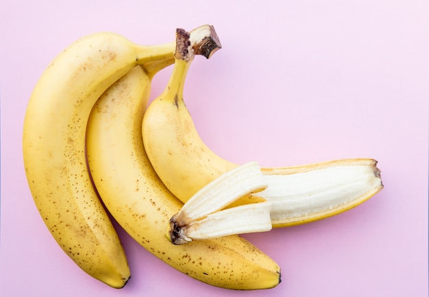 Желтые бананы на четком розовом фоне. вид сверху
