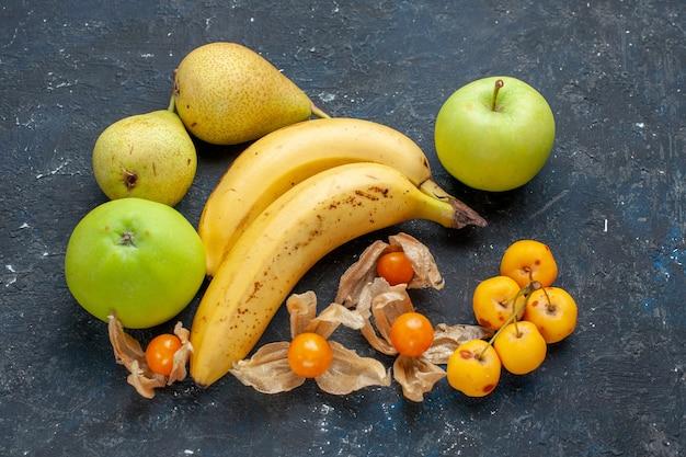 紺色の机の上に青リンゴ梨とベリーの黄色いバナナのペア