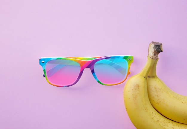 Yellow bananas and sunglasses on clear pink background. above view