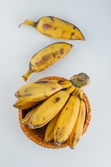 Yellow bananas in a wicker basket on white,
