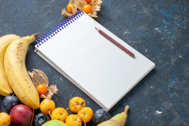 新鮮な青リンゴと黄色のバナナ梨プラムメモ帳と暗い上に甘いサクランボ