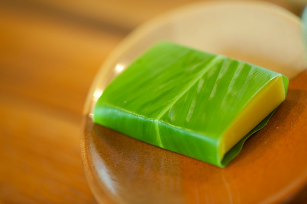 Yellow bar of soap wrapped in a green leaf sitting in a wooden soap dish