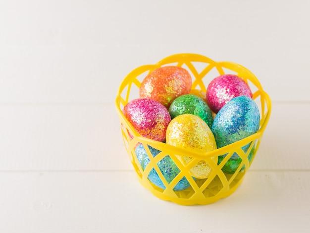 Желтая корзина с красочными яйцами на деревянном столе