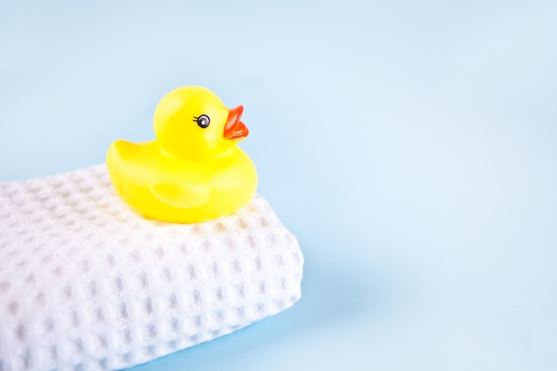 Желтая банная резиновая утка на белом вафельном полотенце