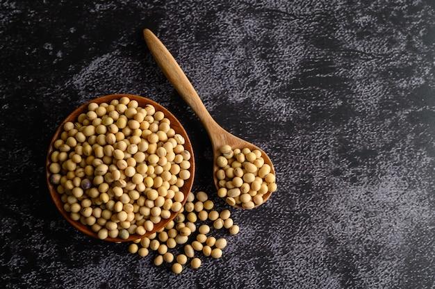 木製のボウルと黒のセメントの床に木のスプーンで黄色の豆。