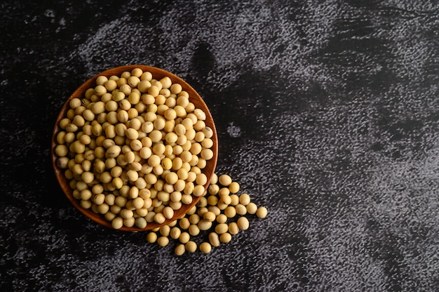 Yellow beans in a wooden bowl on the black cement floor.