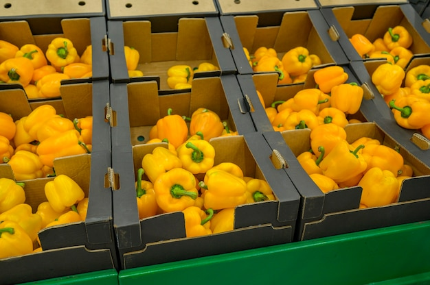 Yellow bell pepper in cardboard boxes of a supermarket