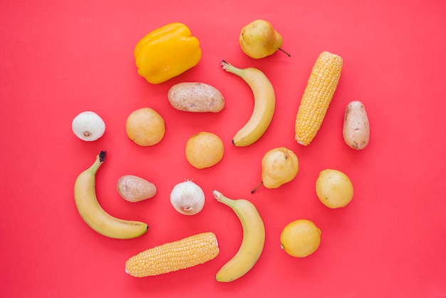 Yellow bell pepper; onion; potato; pears; lime; corn and garlic on red background