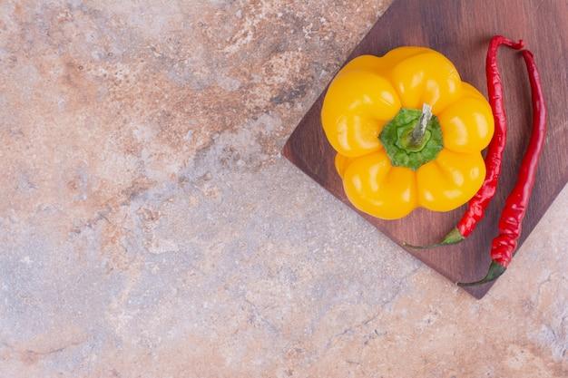 Peperone giallo con peperoncini rossi su una tavola di legno
