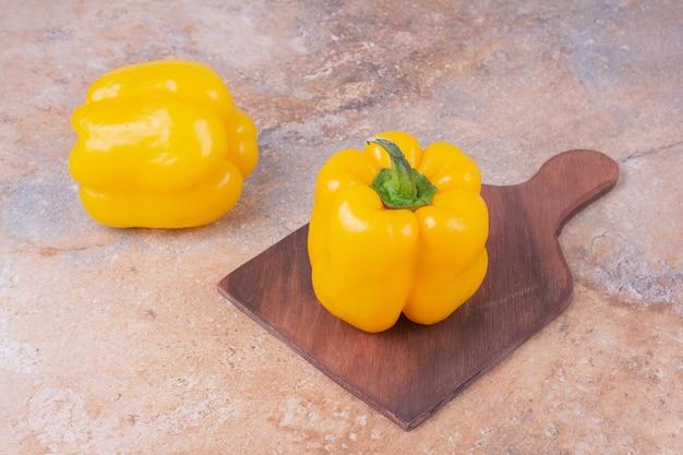 Желтые болгарские перцы на деревянном блюде.