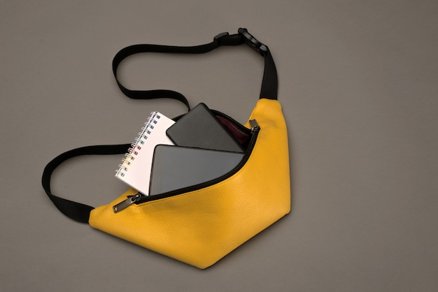 액세서리가있는 노란색 벨트 백 : 메모장, 보조 배터리 및 전화기.