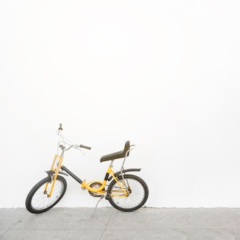 Yellow bicycle parked in front of white wall