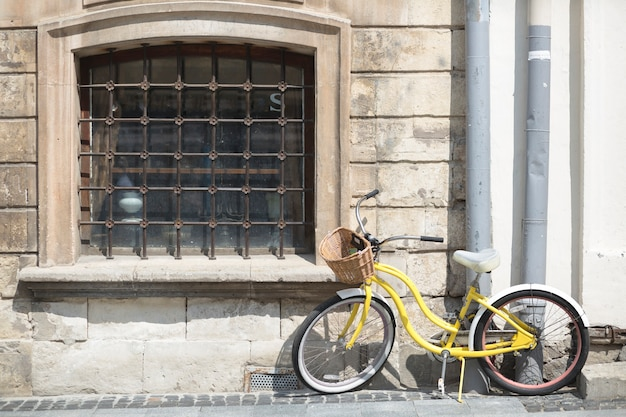Yellow bicycle with basket in front of old wall