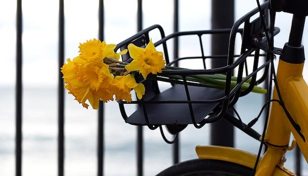 Желтый велосипед с корзиной желтых цветов на улице