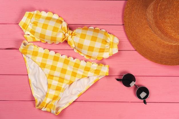 Желтое бикини на ярко-розовом деревянном фоне