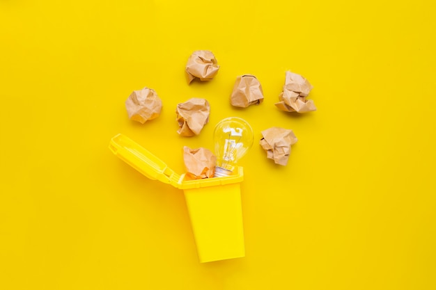 電球と黄色の背景に茶色のしわくちゃの紙の黄色い箱。アイデアと創造的思考の概念。