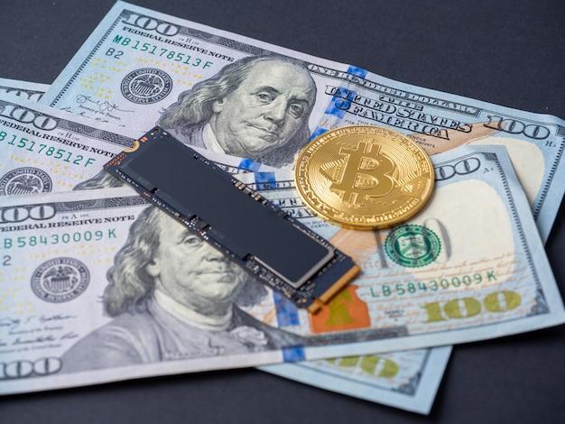 노란색 비트코인, m2 ssd 디스크, 100달러 지폐가 검정색 배경에 놓여 있습니다. 하드 드라이브를 통한 암호화폐 채굴의 개념