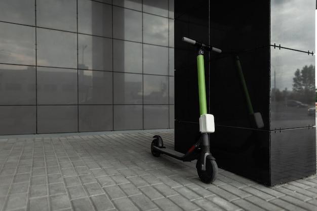 黒い建物の近くの街の通りに、黄黒の電動スクーターが立っています。現代の輸送。