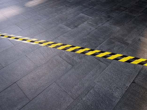 Yellow black safety warning tape on tiled floor covering electrical cable underneath