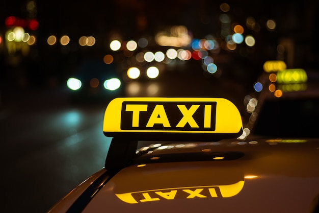 Yellow and black sign of taxi placed on top of a car at night