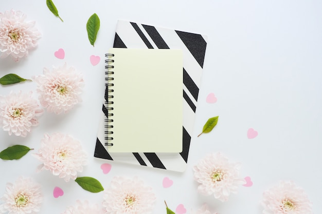 Yellow and black and white notebooks, pink plastic hearts and many pink flowers of chrysanthemums and green leaves on a white table.