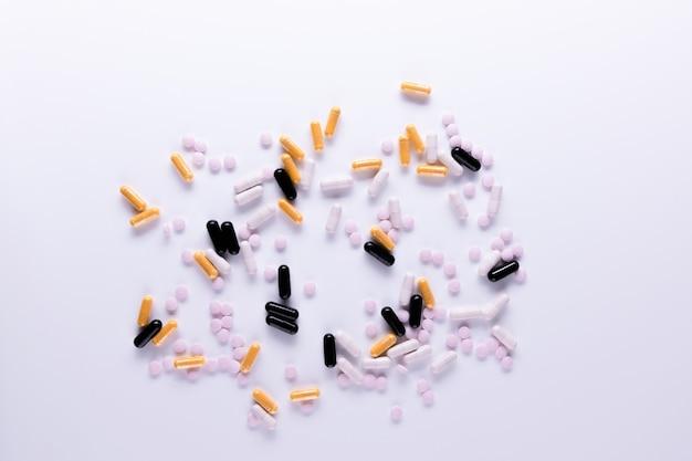 Желтые черные белые таблетки и капсулы, лежащие на белом фоне крупным планом омега