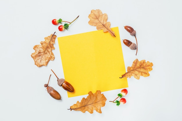 黄色の空白のフレームと白い背景の上のオークの葉とどんぐり。秋のモックアップ。最小限の秋の構成、秋のコンセプト。フラットレイ、トップビュー、コピースペース。
